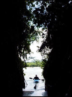 A kayaker pauses near the mouth of a slot canyon.