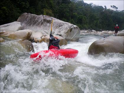Kayaker on a rapid on Rio Piatua, Ecuador.