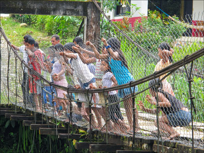Ecuadorian kids on bridge Rio Misahualli.