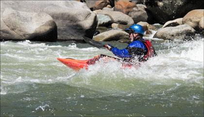 Kayaker surfing wave Rio Quijso, Ecuador
