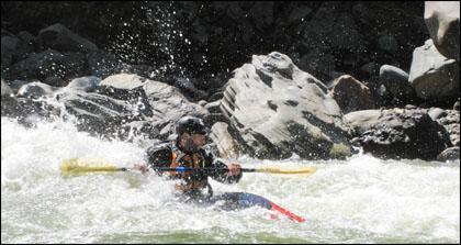 Kayaker surfing wave. Rio Quijos, Ecuador